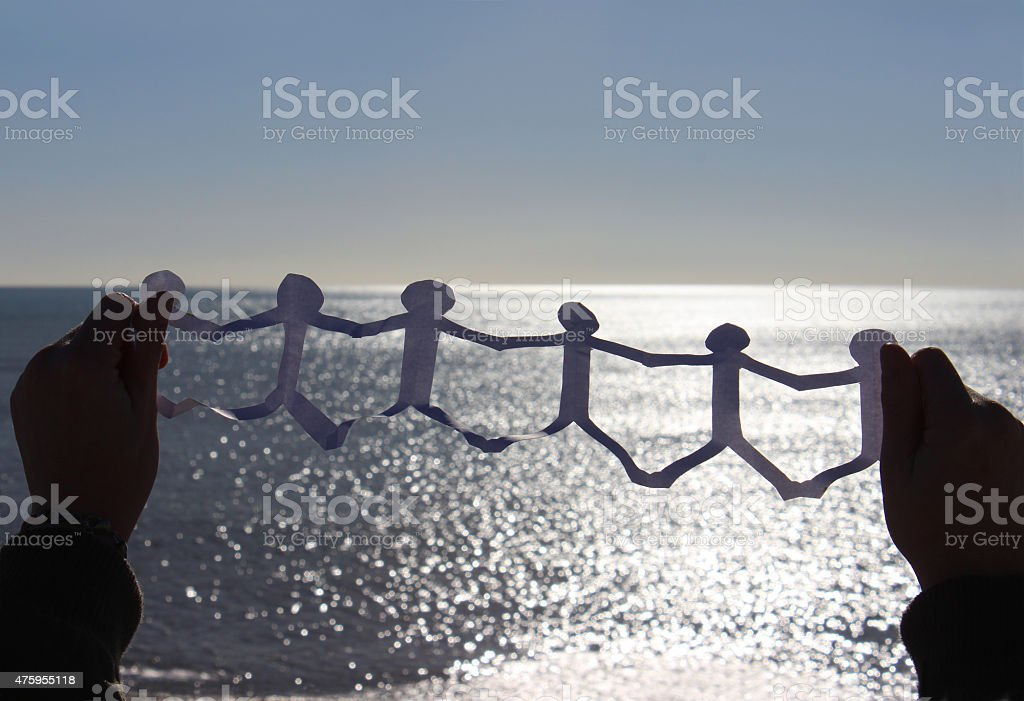 Image of paperchain of cut-out people in-front of sea / sky stock photo