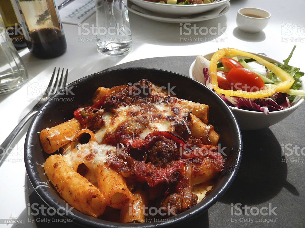Image of penne / rigatoni pasta with meatballs, melted cheese, peppers stock photo