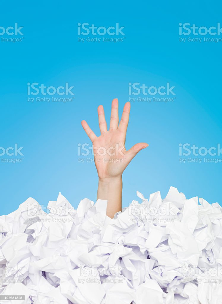 Image of person buried in paper leaving one hand out stock photo