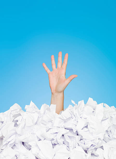 Image of person buried in paper leaving one hand out