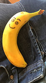 Image of phallus shaped banana penis erection on man's lap with smiley face, denim jeans with unbuttoned trouser flies / zip, funny concept photo of penis health, erectile dysfunction, sexual health, STI sexually transmitted infections and diseases