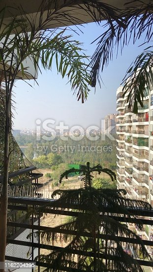 Stock photo of anti-bird netting and spikes on an apartment balcony in Ghaziabad, India with cityscape view in background.