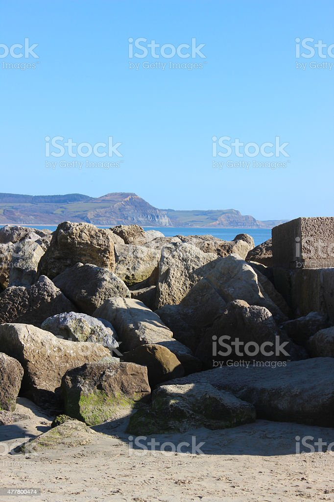 Image of pile of rocks, natural sea defence, beach rock-armour stock photo