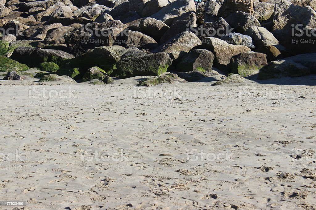 Image of pile of rocks on beach sand, rock-armour / riprap stock photo