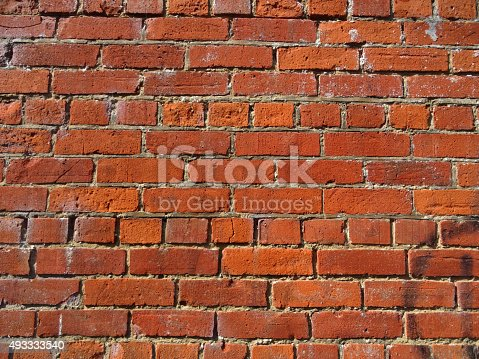 Photo showing a section of a plain, old red brick wall with crumbling brickwork / mortar that is gradually eroding due to years of frosty winter weather.