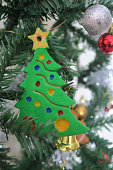Image of plastic artificial Christmas tree with homemade handpainted decorations made from salt dough cookie cutters, baked like cookies, golden star Christmas tree topper painted by hand with acrylic / poster paints, fake Xmas tree decorated fairy lights