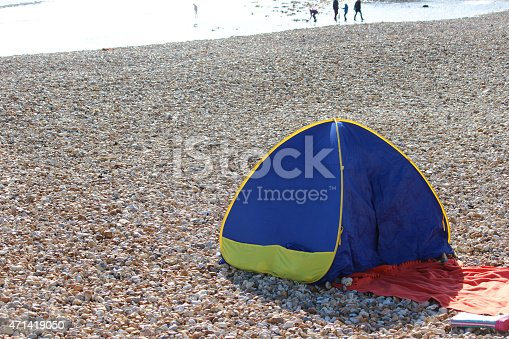 Photo showing a typical seaside holiday scene, with a pebble beach and a popup tent / shelter, which allows young children to shelter out of the harmful sun.