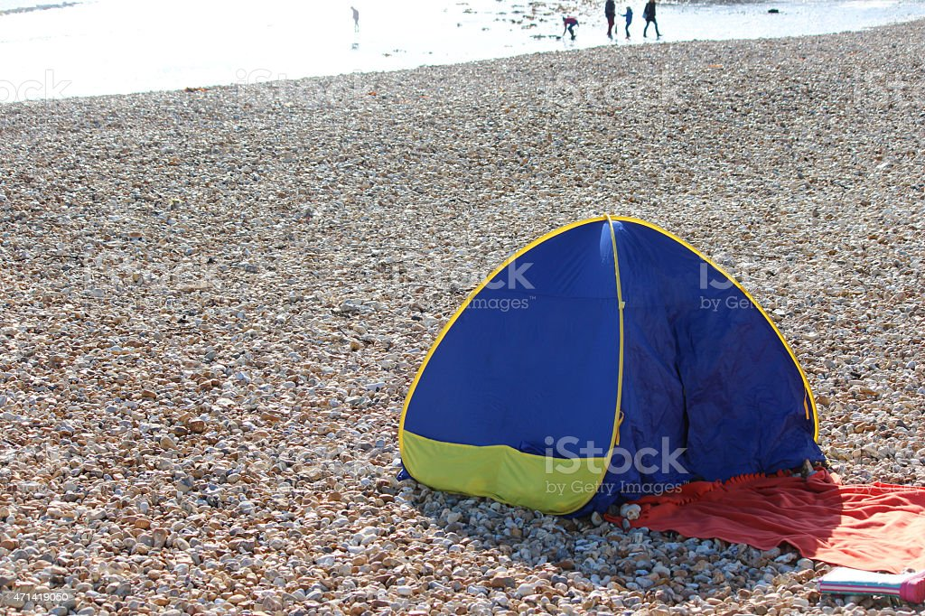 Image of popup beach shelter / tent on pebbles, seaside holiday stock photo