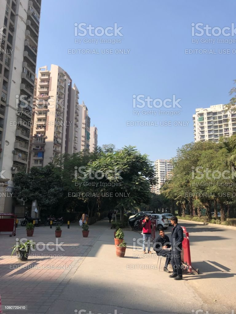 Image of quiet road in Delhi, India, pavement, apartment blocks and security guards stock photo