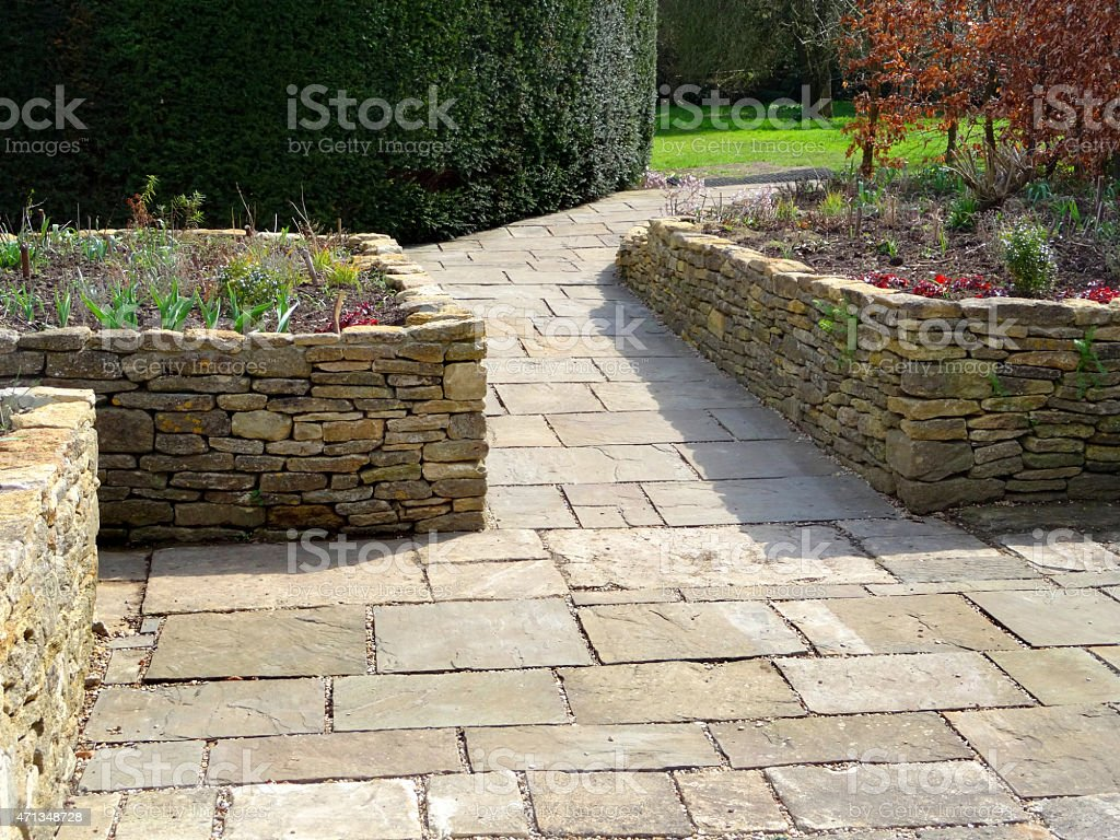 Image of raised garden beds with flagstone paving patio, wheelchair-friendly stock photo