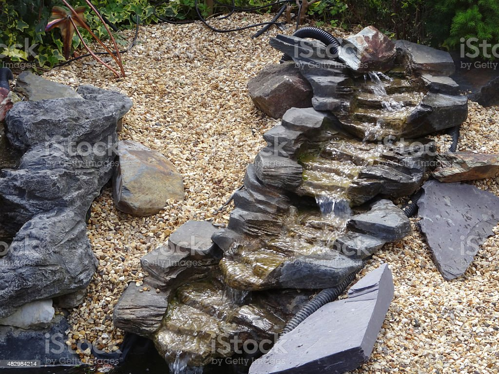 Image of realistic plastic, fibreglass waterfall with pond pump / stones stock photo