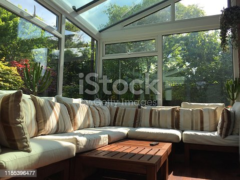 Stock photo of white UPVC conservatory windows with double glazing and glass roof with a beautiful garden view of bonsai trees and blue sky. This conservatory has a sofa with beige and cream cushions, used as inside outside living and dining sun lounge in England, UK
