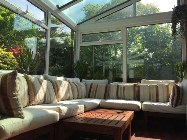 Image of rectangular white UPVC conservatory lean-to glass room with sunny garden views, large double-glazed windows and glass roof with self-cleaning panes / L-shaped corner sofa settle conservatory furniture, coffee table and television TV remote contro stock photo
