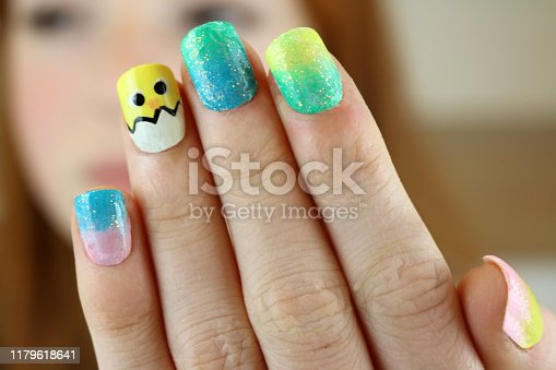 istock Image of red haired teenage girl 14 / 15 holding up fingernails painted with Easter chick springtime design, yellow, blue and pink and black nail varnish, focus on foreground 1179618641