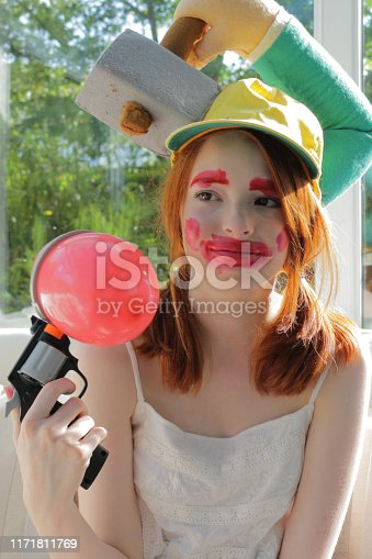 Stock photo showing a beautiful, ginger haired teenager playing an indoor forfeit balloon popping game. As a consequence of bursting a balloon the girl is wearing clown face makeup and a silly novelty hat.