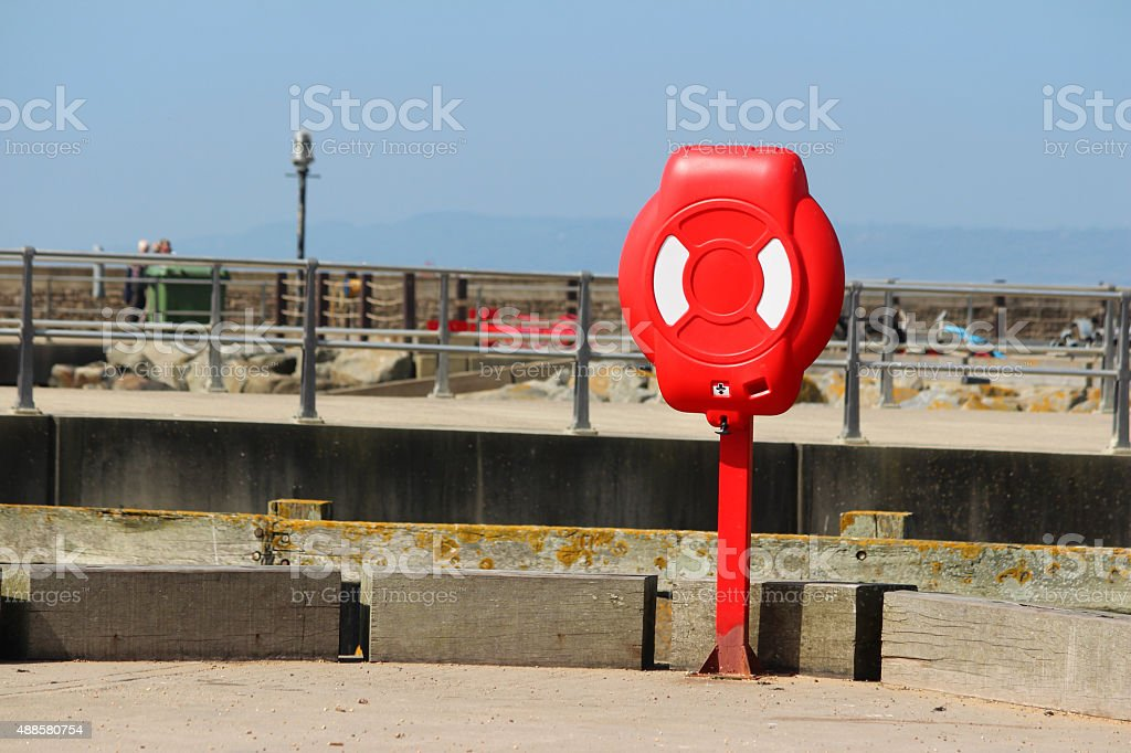 Image of red lifering buoyancy aid at seaside / ring buoy stock photo
