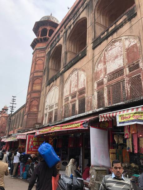 Image of red sandstone Jama Masjid (Friday Mosque), viewed from the maze of lanes in Kinari Bazaar, Agra, Uttar Pradesh, India Kinari Bazaar, Agra, Uttar Pradesh, India - February 14, 2019: Stock photo showing the Kinari bazaar market in Agra, Uttar Pradesh, India, with locals shopping for clothes, saris/ sarees and street food and a view of the Jama Masjid mosque in the background. agra jama masjid mosque stock pictures, royalty-free photos & images