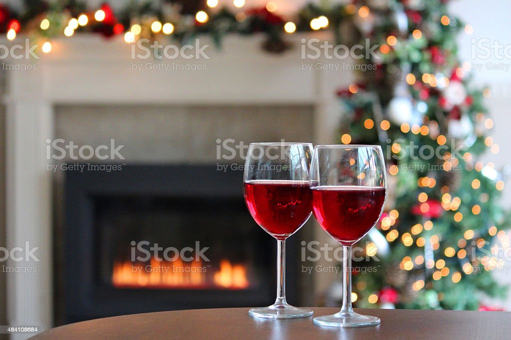 image of red wine glasses gas fire fireplace christmas decorations royalty free