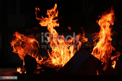 istock Image of roaring, dancing flames from big bonfire, burning wood and cow dung cakes against night sky, Indian festival 1249509226