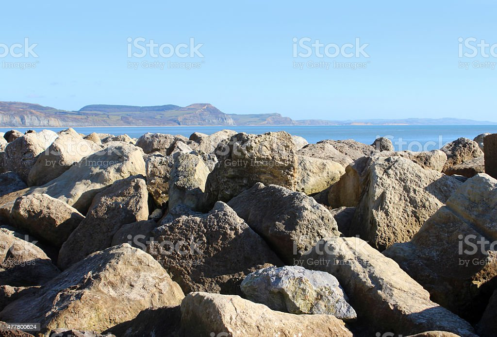 Image of rocks preventing erosion of beach, riprap limestone rock-armour stock photo