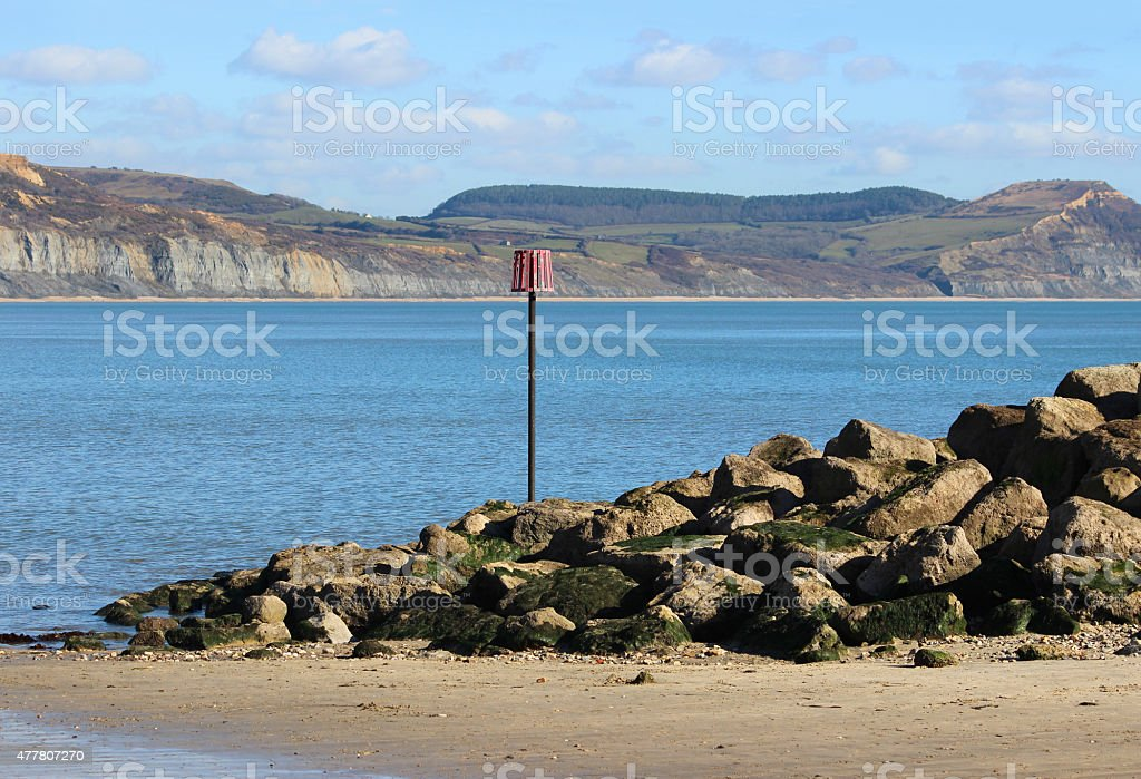 Image of rocky sea defence on beach, coastal erosion rock-armour stock photo