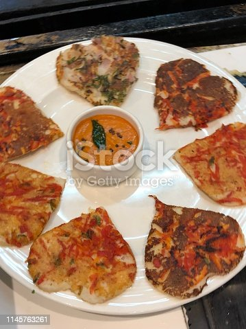 Photo showing an unusual Indian version of a romantic Valentine's Day breakfast, consisting of a selection of different uttapams (Indian savoury pancakes), which is a thick pancake batter, topped with savoury ingredients such as slices onion, tomatoes, green chillies and herbs. February 14th is an important day for couples all over the world, with this romantic Indian breakfast of uttapam hearts being served at a hotel restaurant in New Delhi, India.