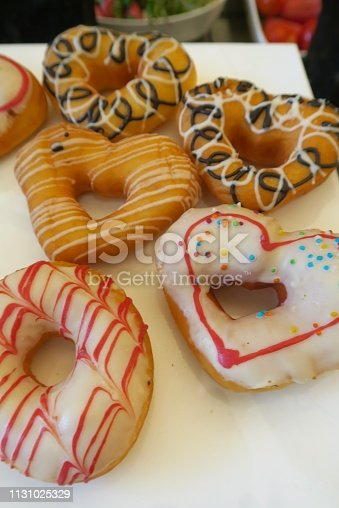 Icing decorated heart-shaped doughnuts displayed on a bakery table, a treat in celebration of Valentine's Day.