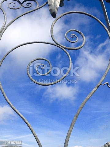 Stock image showing a silver grey coloured gate made using ironwork techniques, with a strong romantic feel since the curves and swirls of the ornate metalwork appear to be forming the shape of love hearts. Located within a formal romance themed garden of red roses and fountains, this metal love heart gate has been photographed against a rich blue sky background with drifting clouds overhead.