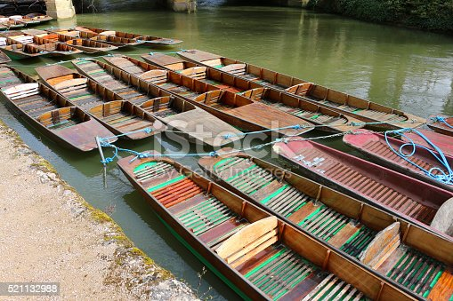 Photo showing wooden punts tethered together with ropes to stop them drifting away on the river. These flat-bottomed boats are propelled by the punter pushing a wooden pole along the river bed.