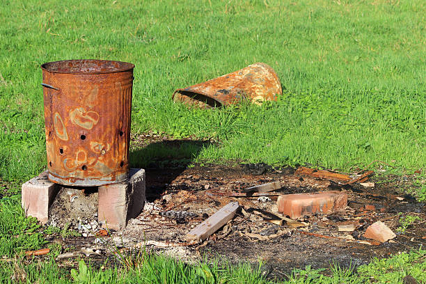 Image of rusty garden waste incinerator bin, on lawn grass Photo showing a rusty garden waste incinerator bin, on lawn grass. This metal bin is regularly used to burn branches, weeds, autumn leaves and general garden waste. dumpster fire stock pictures, royalty-free photos & images