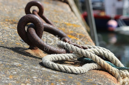 Photo showing a row of rusty iron mooring rings, which are positioned on the top of a stone wall surrounding a harbour, where they are being used to moor boats with thick lengths of rope.