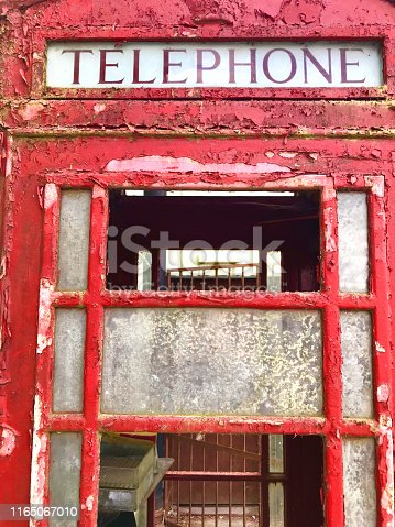 Stock photo of rusty weathered red telephone box with peeling paint windows, broken glass / London phone box decaying and falling apart in state of disrepair needing restoration in junk yard / reclamation yard, English red telephone kiosk in London, England, UK