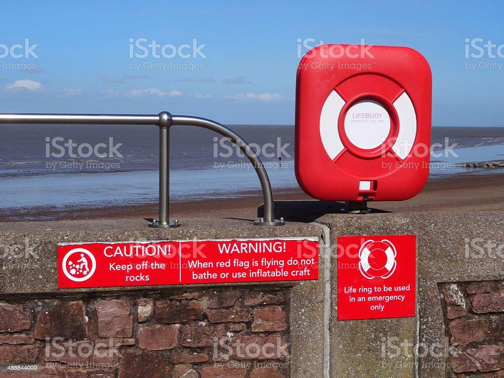 Image of seaside lifebuoy / lifering donut buoyancy aid by beach stock photo