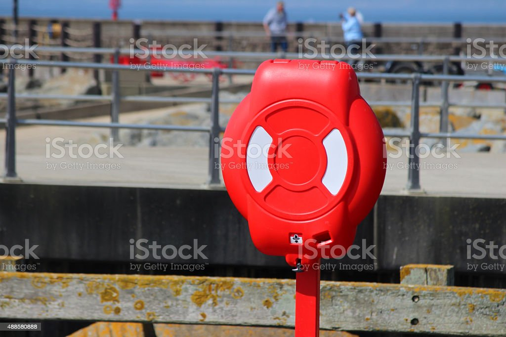 Image of seaside lifering / red life buoy donut at harbour stock photo