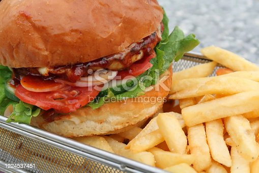 Stock photo of sesame seed bun chicken burger and crispy chunky chips / French fries takeaway food at bar restaurant, unhealthy greasy snack food fried in peanut vegetable oil, served in metal basket.