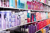 Image of shelves with fashionable modern beautiful stylish conditioners and mousses for hair in the store.