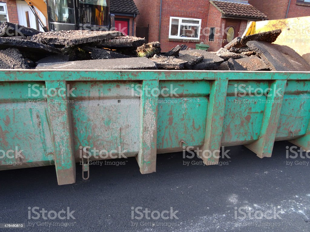 Image of skip filled with dug-up tarmac, pavement being resurfaced stock photo