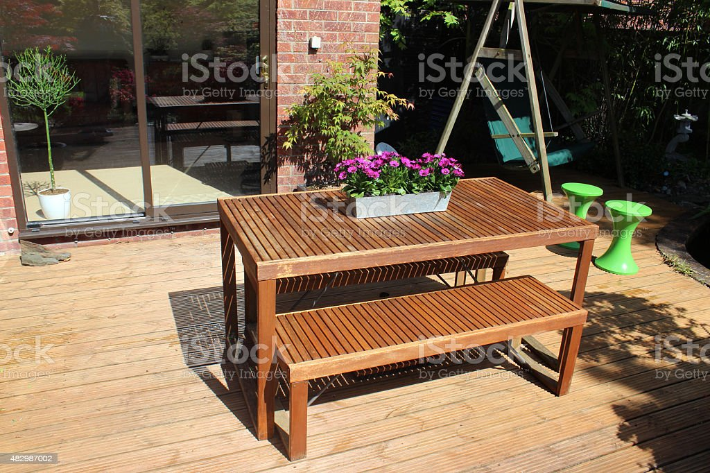 image of slatted wooden table and benches garden furniture on decking royalty free garden furniture