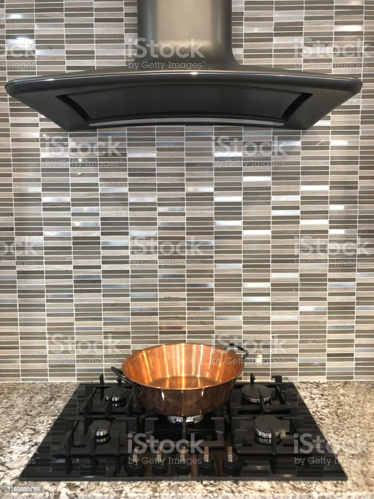 Image Of Small Glossy Grey Mirror Brick Effect Tiling Brick Wall Tiles And Copper Pan Modern Gas Hob Black Kitchen Stove Hot Plates And Metal Curved Cooker Hood Extractor Fan Touch Control