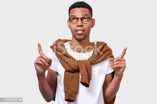 Image of smart African American young man indicates up with two forefingers at blank copy space, for your advertising text, wearing casual outfit and eyeglasses. Advertisement and ethnicity concept