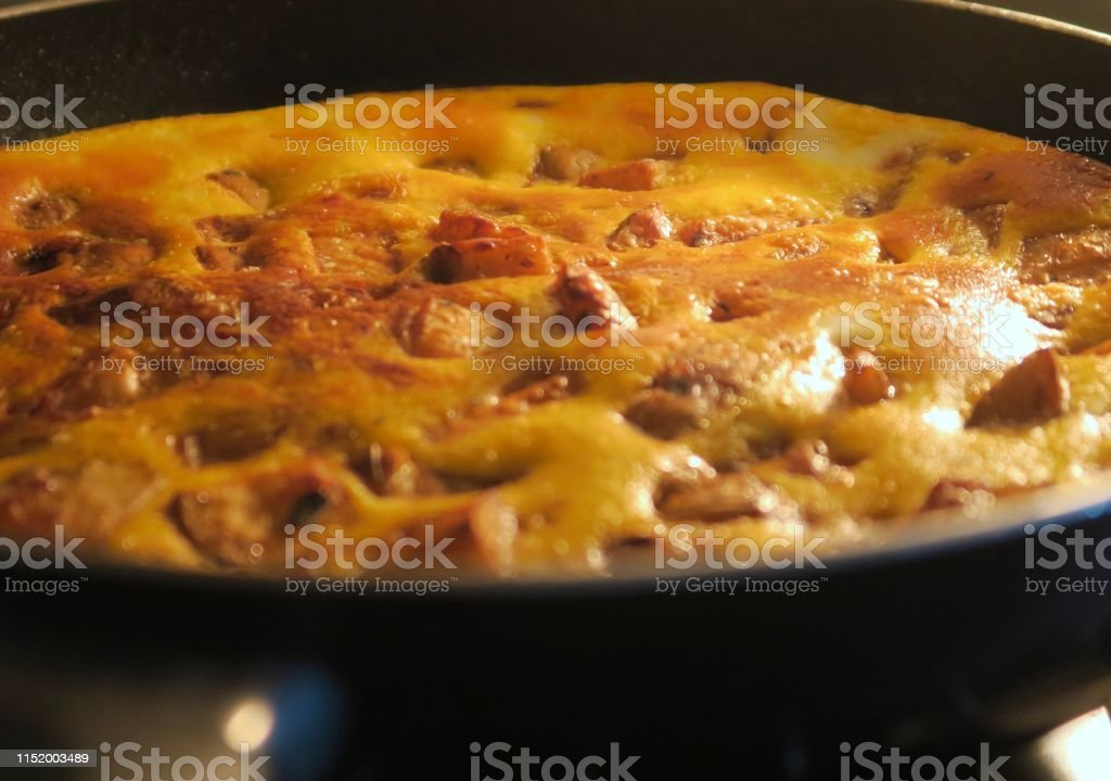 Stock photo of Spanish omelette omelet tortilla cooking in nonstick...