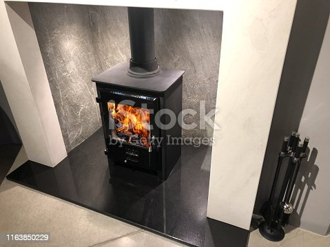 Stock photo of square cast iron woodburner / contemporary log wood burning stove fireplace mantle with orange fire flames burning and generating heat to warm up room instead of gas boiler central heating, modern multifuel stove wood burner stand / chimney flue