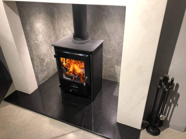 Image of square cast iron woodburner / contemporary log wood burning stove fireplace mantle with orange fire flames burning and generating heat to warm up room instead of gas boiler central heating, modern multifuel stove wood burner stand / chimney flue stock photo