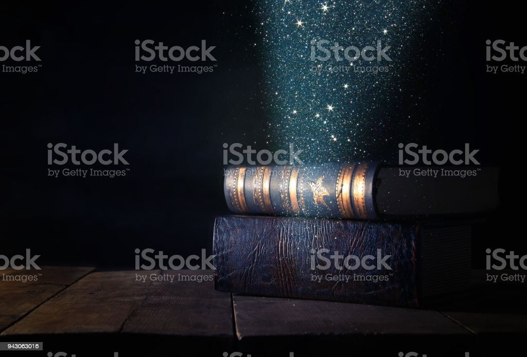 image of stack of antique books over wooden table and dark background. stock photo