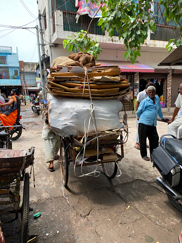 Ghaziabad, Uttar Pradesh, India - August 28, 2021:  Stock photo showing a pile of flattened cardboard boxes being transported on trolley cart to go for recycling.