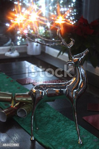 Photo showing a contemporary stainless-steel reindeer stag, where the antlers are doubling up as candle holders for small tealights.