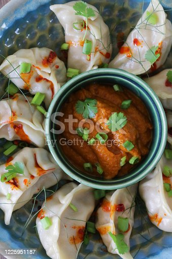 Stock photo showing an evening meal of steamed dumplings (Momos), filled with mixed vegetables and chicken drizzled with chilli oil and garnished with chopped spring onion and coriander leaves on plate with red and orange spicy dipping sauce.