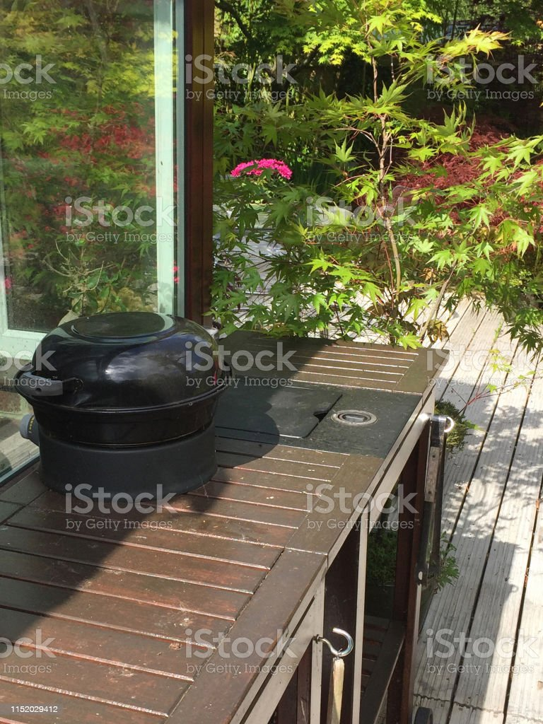 Stock photo of garden decking painted white with pots of flowers,...