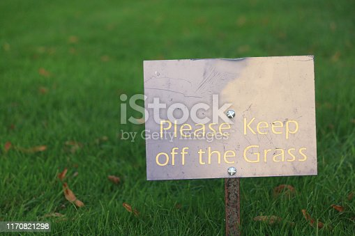 Stock photo of please keep off the grass sign post on sunny shady landscaped green lawn grass, restricted area sign, freshly mowed with push lawnmower and strimmer, lawn care