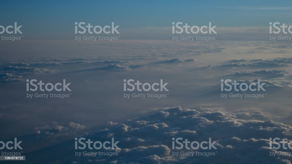 Image of Sunrise above the clouds from airplane window, pune to...